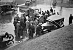 Photograph of a car and truck involved in an accident, with onlookers standing nearby and men assessing the damage, 1929