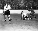 Chicago Blackhawks Glen Skov and Nick Mickoski look on as the crowd cheers a goal by Maurice Richard