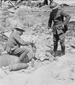 Photograph of a Canadian sitting on and tapping an unexploded shell with a tool while his comrade stands watching, July 1917