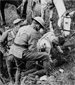Photograph of a Canadian wounded in the shoulder receiving first aid, September 1918